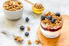 Healthy breakfast from yoghurt with muesli and berries on kitchen table Royalty Free Stock Images
