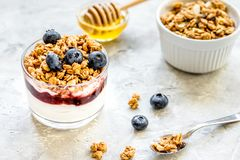 Healthy breakfast from yoghurt with muesli and berries on kitchen table. Healthy fitness breakfast from yoghurt with muesli and blue berries on kitchen table stock photos