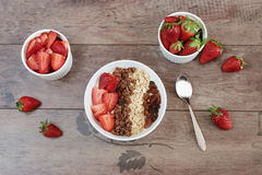 Healthy breakfast -yoghurt with oat flakes, raisins, strawberries, muesli. Fruit breakfast on a wooden background Royalty Free Stock Photo