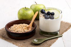 healthy breakfast with yogurt in a glass, fresh green apples, juicy blueberries and toasted oats royalty free stock photography