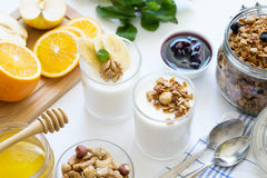 Healthy breakfast with yogurt in glass, granola and fruits Stock Images