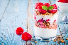 Healthy breakfast: yogurt parfait with granola and fresh raspberries. On rustic background Royalty Free Stock Photo