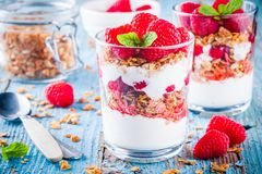 Healthy breakfast: yogurt parfait with granola and fresh raspberries. On rustic background Royalty Free Stock Images