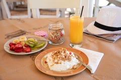 Healthy breakfast from yogurt, sliced banana, kiwi, strawberries, granola and glass of fresh orange juice in a beautiful location royalty free stock image