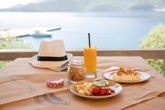 Healthy breakfast from yogurt, sliced banana, kiwi, strawberries, granola and glass of fresh orange juice in a beautiful location stock photos