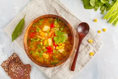 Healthy bright vegetable corn soup in a wooden bowl with flax cr. Healthy bright vegetable corn soup with a root of a herring, pepper, an onion in a wooden bowl royalty free stock photos