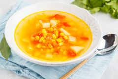 Healthy bright vegetable corn soup in a white plate. Vegan Healthy Food Concept. Top view. Healthy bright vegetable corn soup in a white plate with crispy bread stock photography