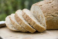 Healthy brown bread. A slice of healthy brown bread on a breadboard Stock Photos