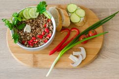 Healthy buckwheat porridge with chopped sweet red pepper. Parsley, sliced cucumber, piece of butter and mushrooms in a white bowl, bread, green onion, slices Stock Image