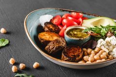 Healthy Buddha bowl dish with avocado, tomato, cheese, chickpea, fresh arugula salad, baked potatoes and sauce pesto. In black background. Dieting food, clean stock images