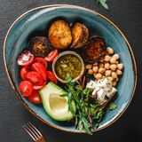 Healthy Buddha bowl dish with avocado, tomato, cheese, chickpea, fresh arugula salad, baked potatoes and sauce pesto in black. Background. Dieting food, clean royalty free stock photo