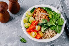 Healthy buddha bowl lunch with grilled chicken, quinoa, spinach, avocado, brussels sprouts, tomatoes, cucumbers  on dark grey back. Ground. Selective focus Stock Image