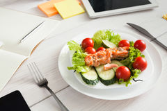 Healthy business lunch snack in office, salmon with vegetables. Healthy business lunch in the office, dish on white wooden desk near tablet and open organizer Stock Photo