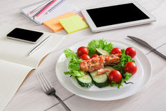 Healthy business lunch snack in office, salmon with vegetables. Healthy business lunch in the office, view of dish on white wooden desk near tablet and open Stock Photography