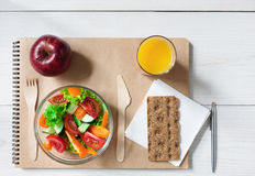 Healthy business lunch snack in office, vegetable salad and coffee. Healthy business lunch in office top view, vegetable salad bowl with wooden cutlery on white Royalty Free Stock Image