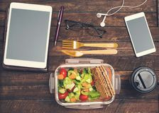 Healthy business lunch at workplace. Salad, salmon, avocado lunch box on working desk with tablet, smartphone, glasses and royalty free stock photos