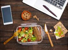 Healthy business lunch at workplace. Salad, salmon, avocado and bread crisps lunch box on working desk with laptop, smartphone stock image