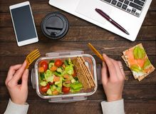Healthy business lunch at workplace. Salad, salmon, avocado and bread crisps lunch box on working desk with laptop, smartphone, stock photography