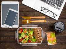 Healthy business lunch at workplace. Salad, salmon, avocado and bread crisps lunch box on working desk with laptop, smartphone, stock images