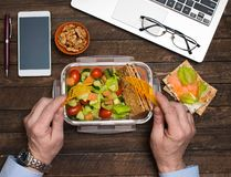 Healthy business lunch at workplace. Salad, salmon, avocado and bread crisps lunch box on working desk with laptop, smartphone, royalty free stock photography
