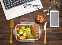 Healthy business lunch at workplace. Salad, salmon, avocado and nuts lunch box on working desk with laptop, smartphone, glasses royalty free stock image