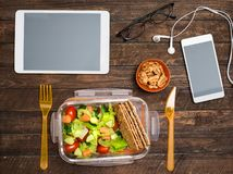 Healthy business lunch at workplace. Salad, salmon, avocado and nuts lunch box on working desk with tablet computer smartphone stock photo