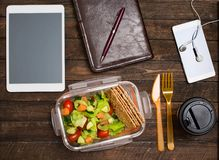 Healthy business lunch at workplace. Salad, salmon, avocado and nuts lunch box on working desk with tablet computer, smartphone, royalty free stock photography