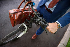 Healthy businessman cycling with bag Stock Images