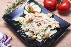 Healthy caesar salad on the black plate Royalty Free Stock Photo