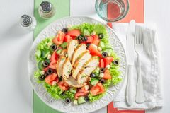 Healthy Caesar salad with chicken, olives and tomatoes stock photo