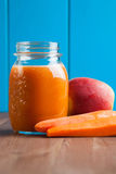 Healthy carrot apple smoothie in a jar on blue wooden background Stock Photo