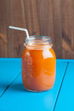 Healthy carrot apple smoothie in a jar on blue wooden background Royalty Free Stock Photo