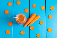 Healthy carrot smoothie in a jar on blue wooden background. Top view Stock Image