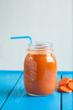 Healthy carrot smoothie in a jar on blue wooden background. Vegetable drink Stock Image