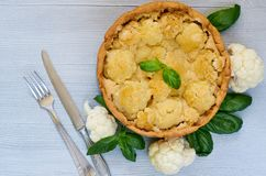 Healthy cauliflower pie decorated with fresh basil leaves and vintage silver knife and fork. Vegetarian cauliflower tart stock images