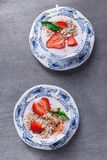Healthy cereal with strawberries and yogurt decorate with mint in a ceramic bowls on wooden table. Granola, muesli Royalty Free Stock Photography