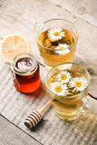 Healthy chamomile tea poured into glass cup. Teapot, small honey jar, heather bunch and glass jar of daisy medicinal herbs royalty free stock photo