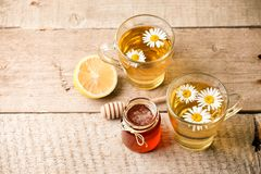 Healthy chamomile tea poured into glass cup. Teapot, small honey jar, heather bunch and glass jar of daisy medicinal herbs stock photography