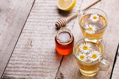 Healthy chamomile tea poured into glass cup. Teapot, small honey jar, heather bunch and glass jar of daisy medicinal herbs stock image