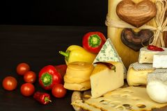 Healthy cheese. Different types of cheeses with tomato and chili pepper on the kitchen board. Preparation of healthy food. Healthy cheese. Different types of stock images