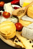Healthy cheese. Different types of cheeses with tomato and chili pepper on the kitchen board. Preparation of healthy food. Healthy cheese. Different types of Stock Photography
