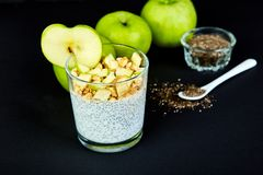 Healthy chia pudding with apples and granola in glass. Royalty Free Stock Photo