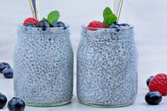 Healthy chia pudding with berries in a glass jar on wooden table Stock Images