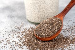 Healthy Chia seeds in a wooden spoon and chia pudding in glass j stock image