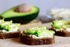 Healthy chickpeas hummus and avocado sandwiches on a wooden board, avocado half, hummus in a glass bowl. Veggie sandwiches Stock Photo
