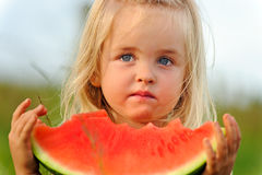 Healthy child eating watermelon Stock Photos