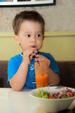 Healthy child with fresh carrot juice Stock Photography
