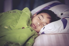 Healthy child. Little asian boy sleeping peacefully on bed. Royalty Free Stock Image