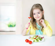 Healthy child nutrition.Girl eating salad at table. Royalty Free Stock Photos