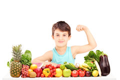 Healthy child showing his arm muscles and sitting on a table ful. L of pile of fruits and vegetables Stock Photography